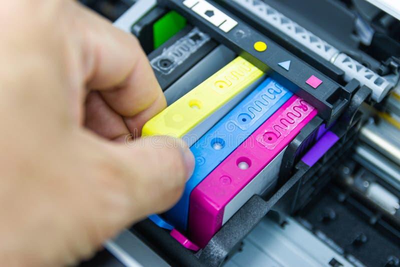 Οι τεχνικοί εγκαθιστούν την κασέτα Inkjet εκτυπωτών χρώματος στοκ εικόνες