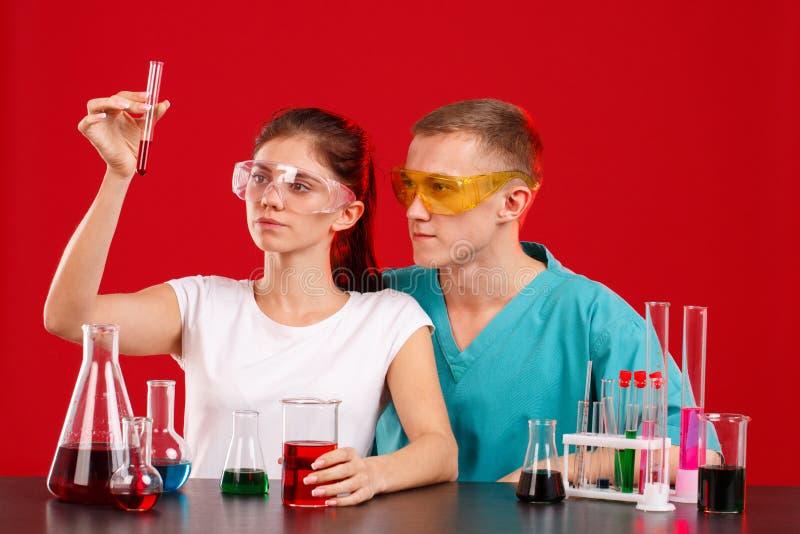 Οι τεχνικοί εργαστηρίων, ένα κορίτσι και ένας τύπος, εξετάζουν το κόκκινο υγρό σε μια διαφανή φιάλη ότι το κορίτσι κρατά υπό εξέτ στοκ φωτογραφίες