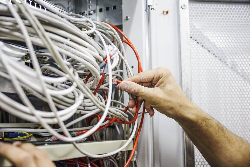 Οι τεχνικοί μεταστρέφουν το οπτικό καλώδιο στοιχείων στο δωμάτιο κεντρικών υπολογιστών δικτύων, υλικό τεχνολογίας Διαδικτύου στοκ εικόνες