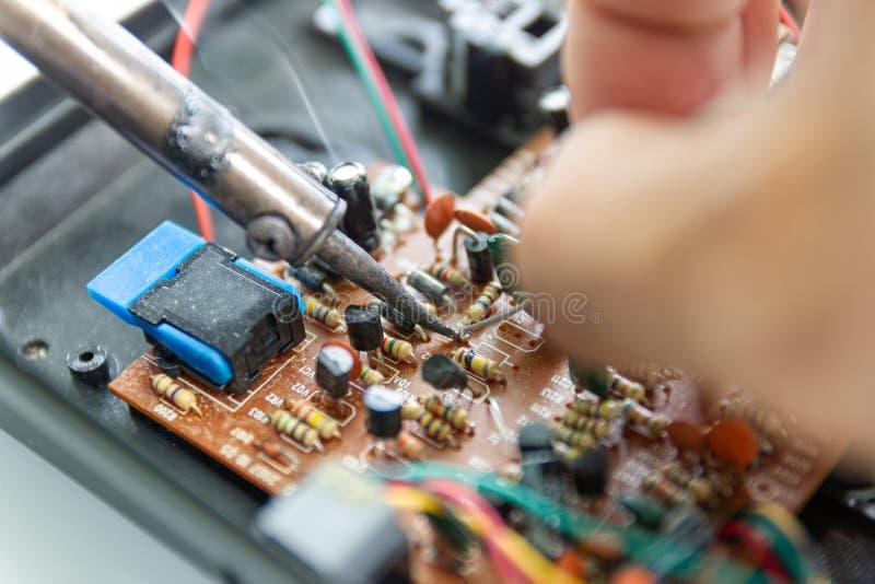 Οι τεχνικοί χρησιμοποιούν έναν συγκολλώντας σίδηρο για την επισκευή ηλεκτρονική στοκ εικόνες
