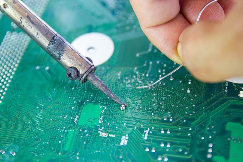 Οι τεχνικοί χρησιμοποιούν έναν συγκολλώντας σίδηρο για την επισκευή ηλεκτρονική στοκ φωτογραφίες