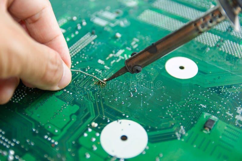 Οι τεχνικοί χρησιμοποιούν έναν συγκολλώντας σίδηρο για την επισκευή ηλεκτρονική στοκ εικόνα με δικαίωμα ελεύθερης χρήσης