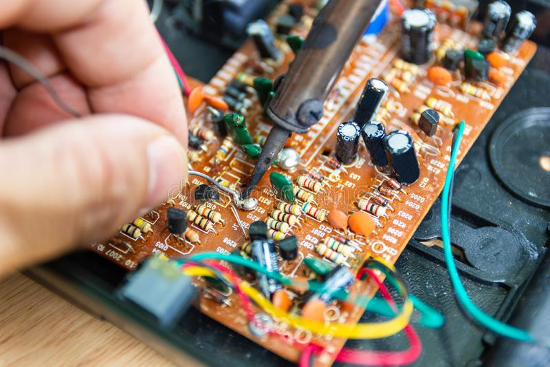 Οι τεχνικοί χρησιμοποιούν έναν συγκολλώντας σίδηρο για την επισκευή ηλεκτρονική στοκ εικόνες με δικαίωμα ελεύθερης χρήσης