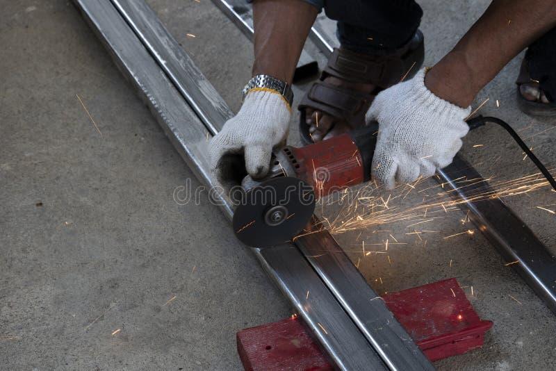 Οι τεχνικοί χρησιμοποιούν τις αλέθοντας μηχανές για να κόψουν τους σωλήνες χάλυβα στοκ εικόνες