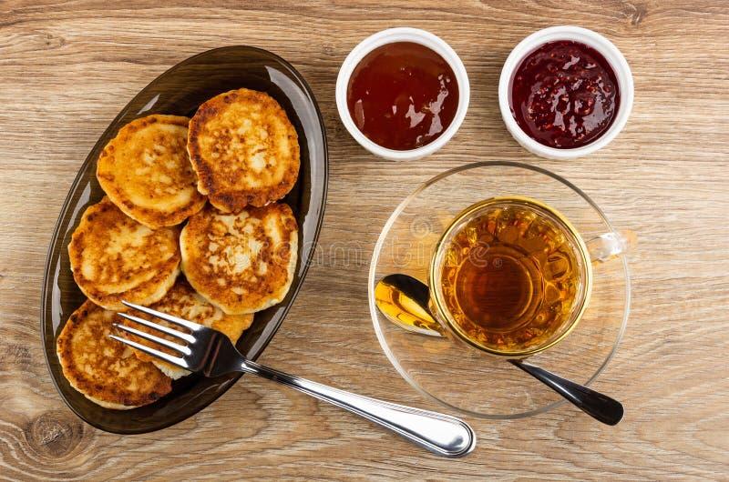 Οι τηγανίτες από το τυρί εξοχικών σπιτιών στο καφετί πιάτο, κύπελλα με το σμέουρο φράσσουν, μαρμελάδα βερίκοκων, δίκρανο, φλυτζάν στοκ φωτογραφίες