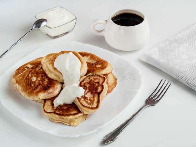 Οι τηγανίτες που γεμίζονται με την ξινή κρέμα βρίσκονται σε ένα άσπρο πιάτο στοκ εικόνες