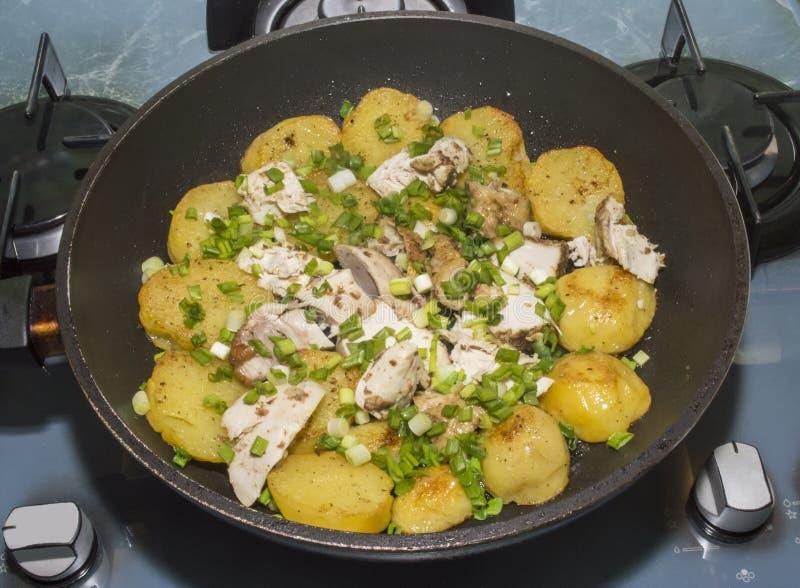 Οι τηγανισμένα πατάτες και το κοτόπουλο με τα πράσινα κρεμμύδια στοκ εικόνα με δικαίωμα ελεύθερης χρήσης