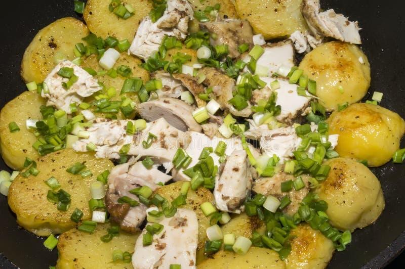 Οι τηγανισμένα πατάτες και το κοτόπουλο με τα πράσινα κρεμμύδια στοκ εικόνα