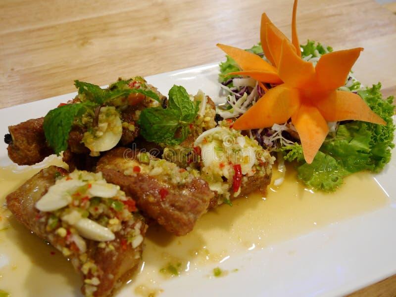 Οι τηγανισμένες μπριζόλες χοιρινού κρέατος με το σκόρδο και το πιπέρι αναμιγνύουν με την πικάντικη σαλάτα στο πιάτο στον πίνακα σ στοκ εικόνα