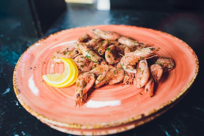 Οι τηγανισμένες ψημένες γαρίδες στο πιάτο με το λεμόνι πρασινίζουν το σκόρδο μαϊντανού στοκ εικόνα με δικαίωμα ελεύθερης χρήσης