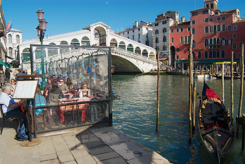 Οι τουρίστες έχουν το μεσημεριανό γεύμα στο πεζούλι καφέδων εν όψει της γέφυρας ορόσημων Ponte Di Rialto πέρα από το μεγάλο κανάλ στοκ φωτογραφία με δικαίωμα ελεύθερης χρήσης