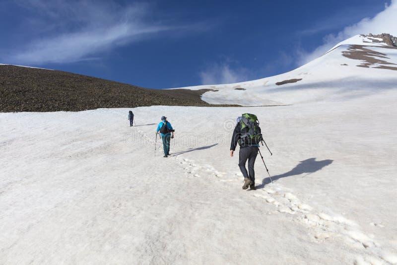 Οι τουρίστες ανέρχονται επάνω mountainside στη χιονοσκεπή σύνοδο κορυφής στοκ εικόνα