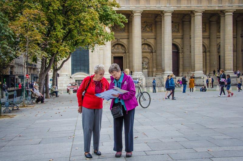 Οι τουρίστες ελέγχουν το χάρτη τους στη θέση ST Sulpice στοκ φωτογραφία