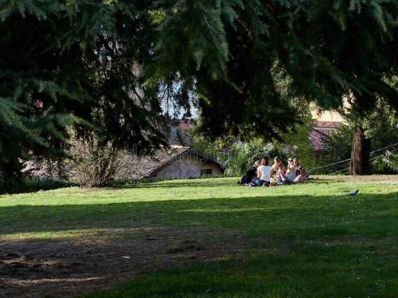 Οι τουρίστες νέων κοριτσιών του Μπελάτζιο, Ιταλία στις 30 Μαρτίου 2019 κάθονται στους μάρτυρες του πάρκου ελευθερίας στο ηλιοβασί στοκ εικόνες