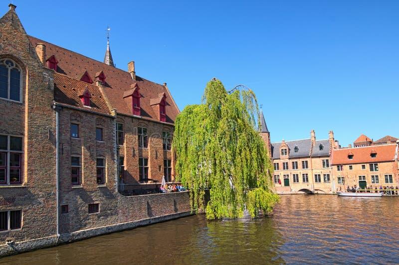 Οι τουρίστες περιμένουν δωρεάν τη βάρκα τουριστών Όμορφο κανάλι και παλαιά, παραδοσιακά σπίτια στην πόλη της Μπρυζ στοκ εικόνες