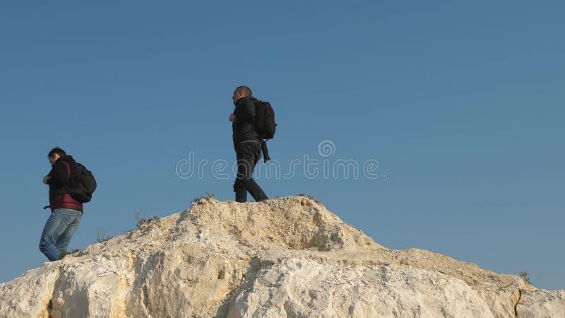Οι τουρίστες πηγαίνουν κατευθείαν στην κορυφή του λόφου ενάντια στον ουρανό r τρεις ορειβάτες αναρριχούνται σε ενός κατόπιν στοκ εικόνες