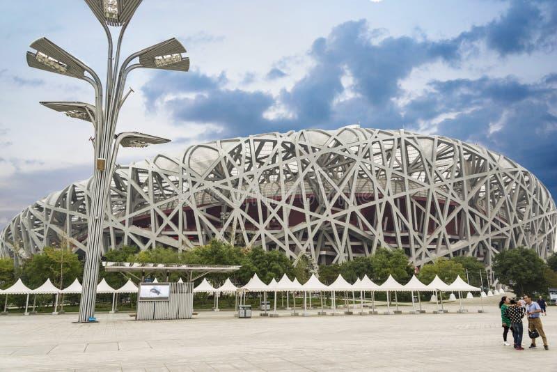 Οι τουρίστες που επισκέπτονται και που παίρνουν τις φωτογραφίες μπροστά από το εθνικό στάδιο του Πεκίνου κάλεσαν επίσης τη φωλιά  στοκ φωτογραφία με δικαίωμα ελεύθερης χρήσης