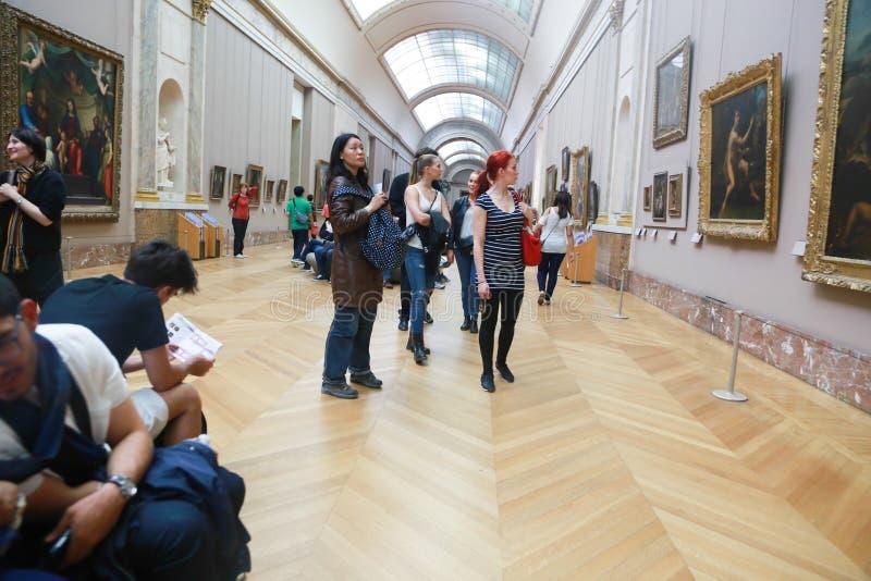 Οι τουρίστες προσέχουν τη διάσημη ζωγραφική στο Λούβρο Παρίσι στοκ εικόνα με δικαίωμα ελεύθερης χρήσης