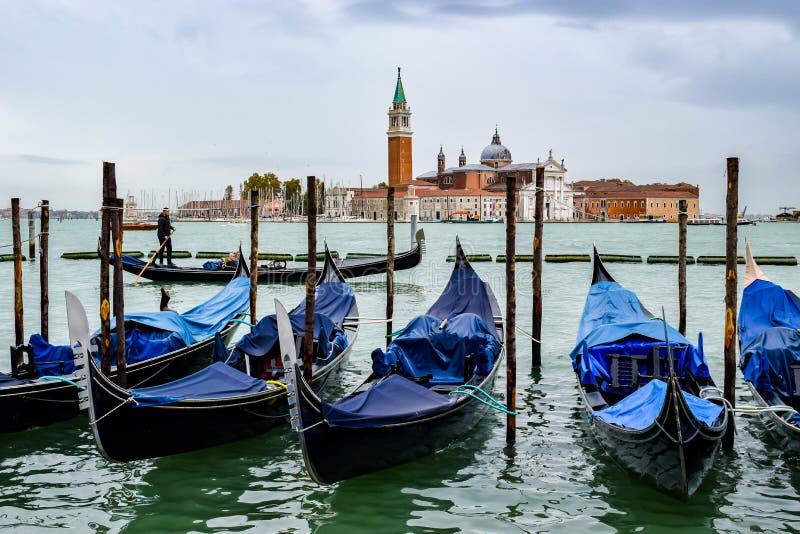 Οι τουρίστες στη βάρκα γονδολών οδηγούν μεταξύ των κενών ελλιμενισμένων γονδολών και της εκκλησίας του SAN Giorgio Maggiore στο υ στοκ φωτογραφίες