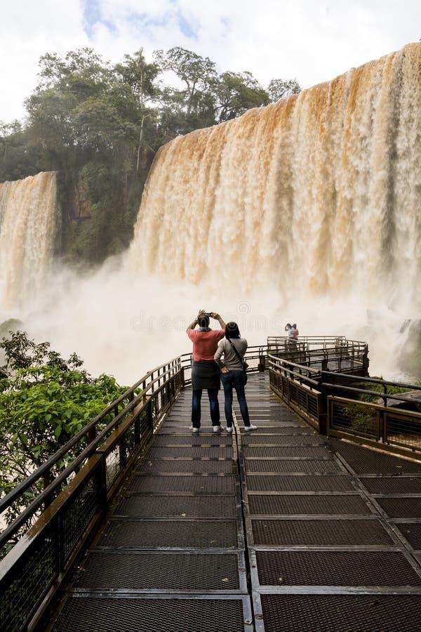 Οι τουρίστες στη γέφυρα για πεζούς στο iguazu πέφτουν veiw από την Αργεντινή στοκ εικόνα