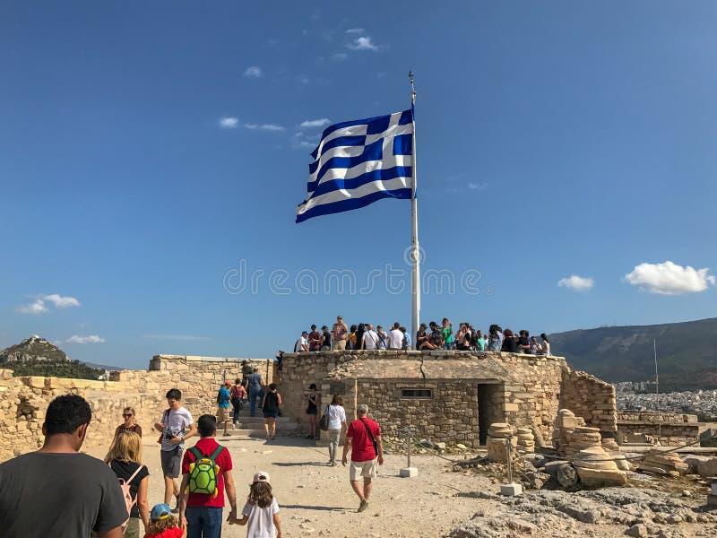 Οι τουρίστες συλλέγουν κάτω από την ελληνική σημαία στην ακρόπολη, Αθήνα, Ελλάδα, ο στοκ φωτογραφία