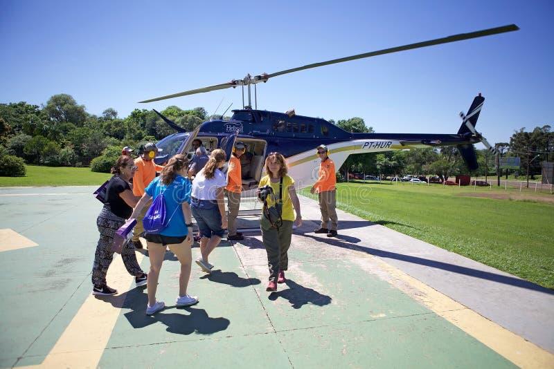 Οι τουρίστες τρέπονται σε φυγή ελικοπτέρων πέρα από Iguazu, Βραζιλία στοκ εικόνες