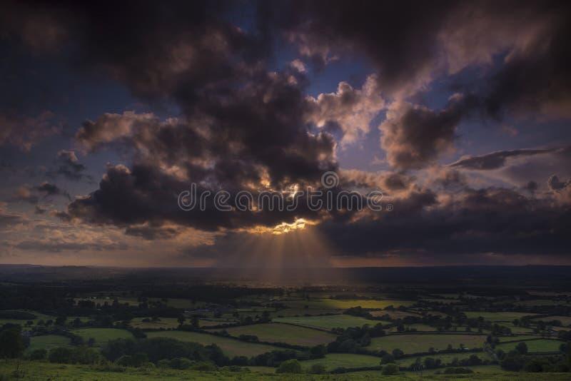 Οι του λυκόφωτος ακτίνες του φωτός του ήλιου λάμπουν επάνω στους τομείς στο Dorset στοκ εικόνες
