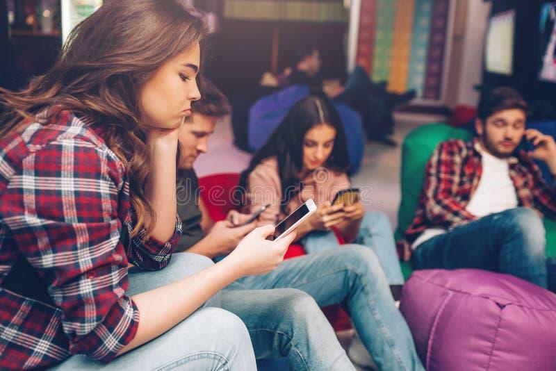 Οι τρυπημένοι νέοι κάθονται στο δωμάτιο παιχνιδιού και εξετάζουν τα phoens στα χέρια Μια συζήτηση τύπων που χρησιμοποιεί το κινητ στοκ εικόνα με δικαίωμα ελεύθερης χρήσης