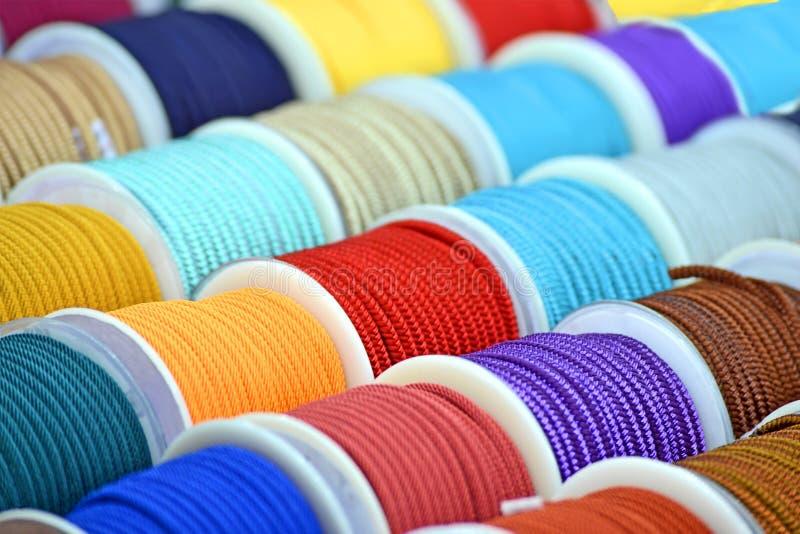 Οι υφαντικές σπείρες σκοινιού ουράνιων τόξων συσκευάζουν το σωρό στον τοίχο, ποικιλομορφία σειρών βιομηχανίας, στοκ εικόνες