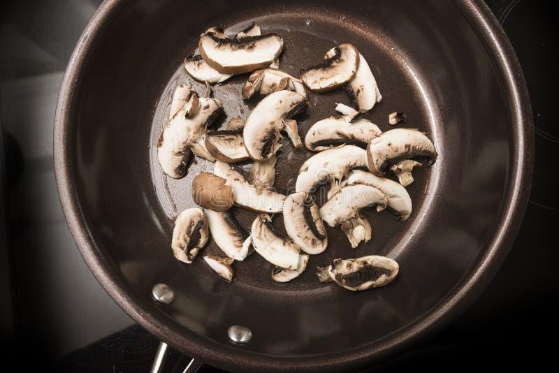 Οι φέτες μανιταριών είναι τηγανισμένες σε ένα μαγειρεύοντας τηγάνι στη μαύρη σόμπα, χ στοκ εικόνα