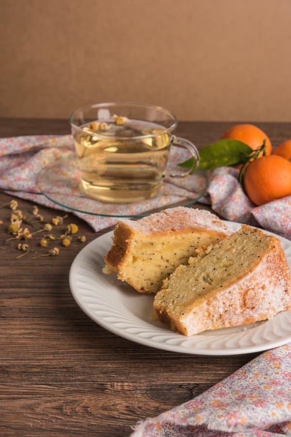 Οι φέτες της κλημεντίνης συσσωματώνουν με το κονιοποιημένα κάλυμμα ζάχαρης και το φλυτζάνι του chamomile τσαγιού Κέικ σε ένα πιάτ στοκ εικόνα με δικαίωμα ελεύθερης χρήσης