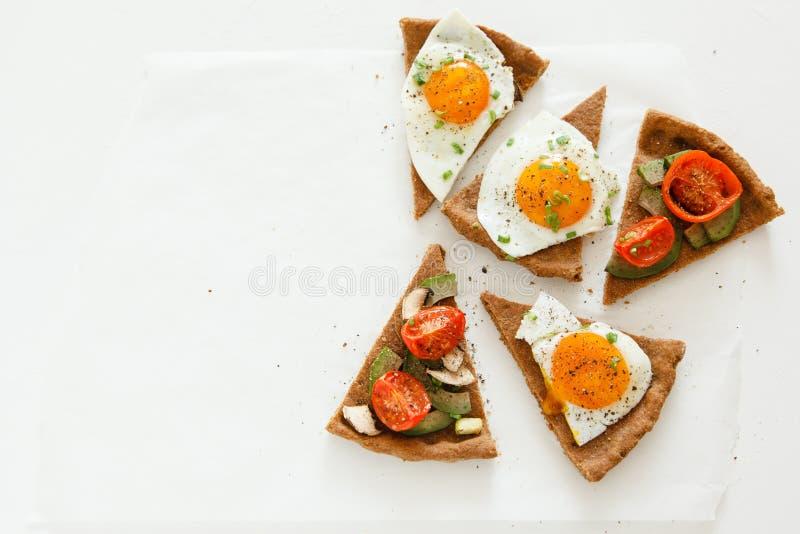 Οι φέτες της πίτας παρόμοιες με την πίτσα με τα λαχανικά, το αυγό και το αβοκάντο βρίσκονται στο άσπρο υπόβαθρο, τοπ άποψη στοκ εικόνες με δικαίωμα ελεύθερης χρήσης