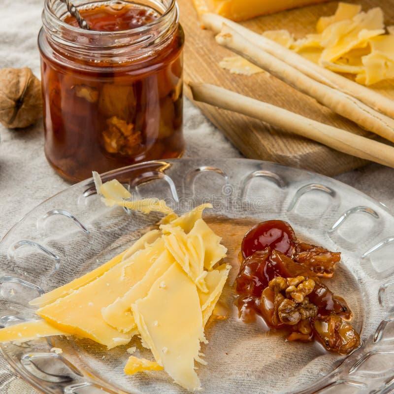Οι φέτες του τυριού με τη μαρμελάδα και των ξύλων καρυδιάς στο πιάτο γυαλιού στοκ εικόνες