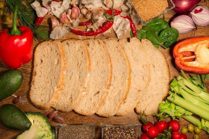 Οι φέτες του ψωμιού μαγιάς πέφτονται απότομα στο κέντρο του πλαισίου Τα διάφορα ζωηρόχρωμα και φρέσκα λαχανικά τακτοποιούνται γύρ στοκ εικόνες