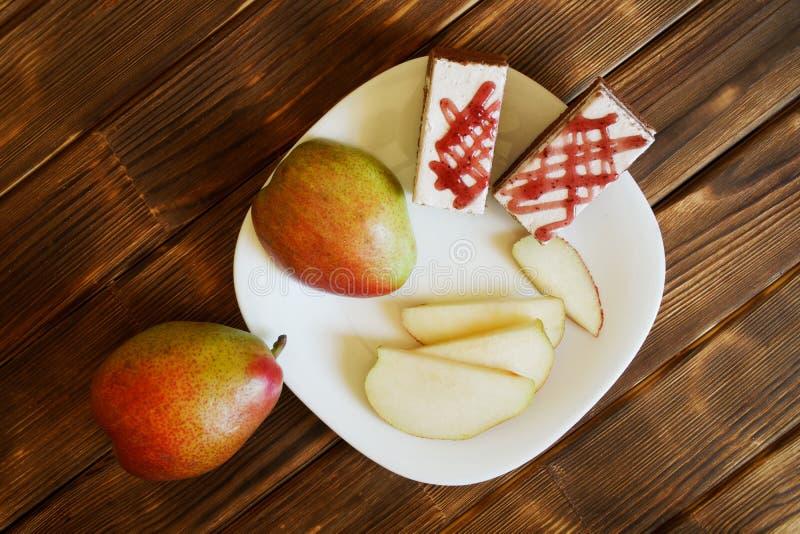 Οι φέτες των κόκκινων αχλαδιών και των σπιτικών κέικ είναι σε ένα άσπρο πιάτο σε έναν ξύλινο πίνακα φιαγμένο από πίνακες πεύκων Μ στοκ φωτογραφία με δικαίωμα ελεύθερης χρήσης