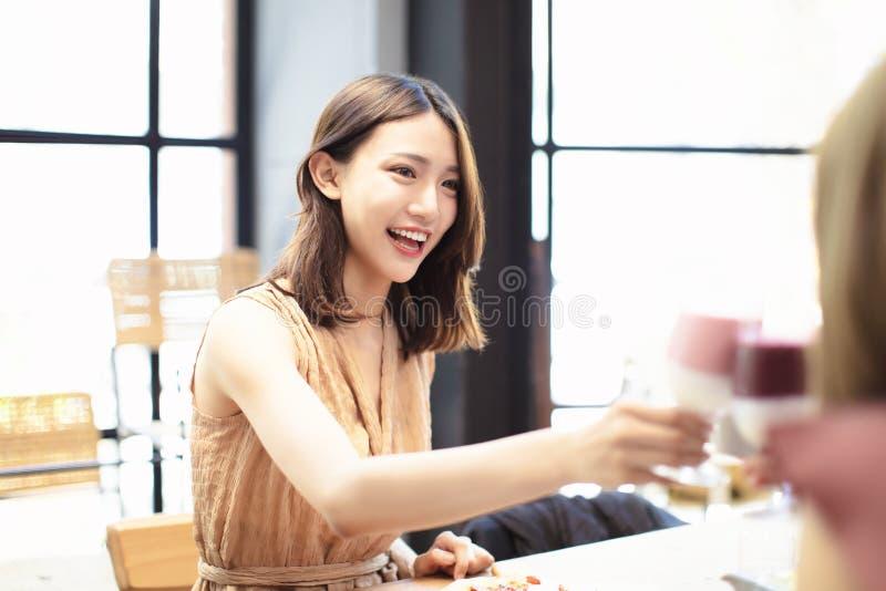 Οι φίλοι γιορτάζουν με τη φρυγανιά και το κουδούνισμα στο εστιατόριο στοκ εικόνες