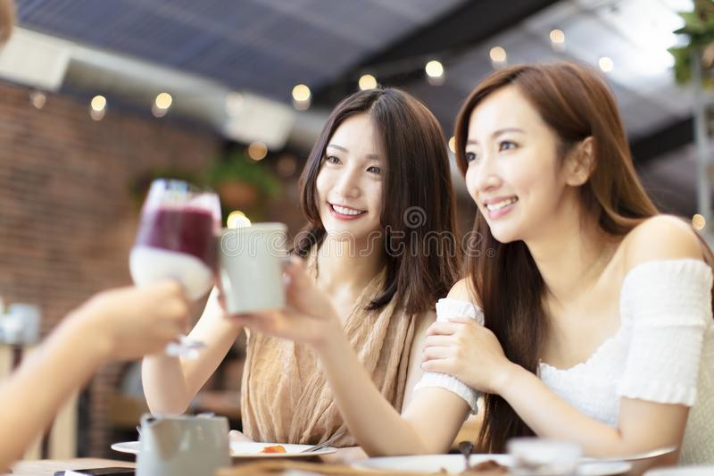 Οι φίλοι γιορτάζουν με τη φρυγανιά και το κουδούνισμα στο εστιατόριο στοκ εικόνα