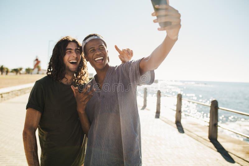 Οι φίλοι κάνουν ένα selfie στο πολυσύχναστο μέρος παραλιών στοκ εικόνες