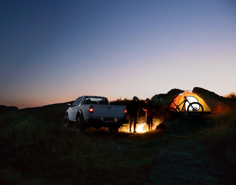 Οι φίλοι κοντά στη φωτιά, το ανοιχτό φορτηγό, τη σκηνή και το ποδήλατο στρατοπεδεύουν τη νύχτα στα βουνά Έννοια περιπέτειας και τ στοκ φωτογραφία με δικαίωμα ελεύθερης χρήσης
