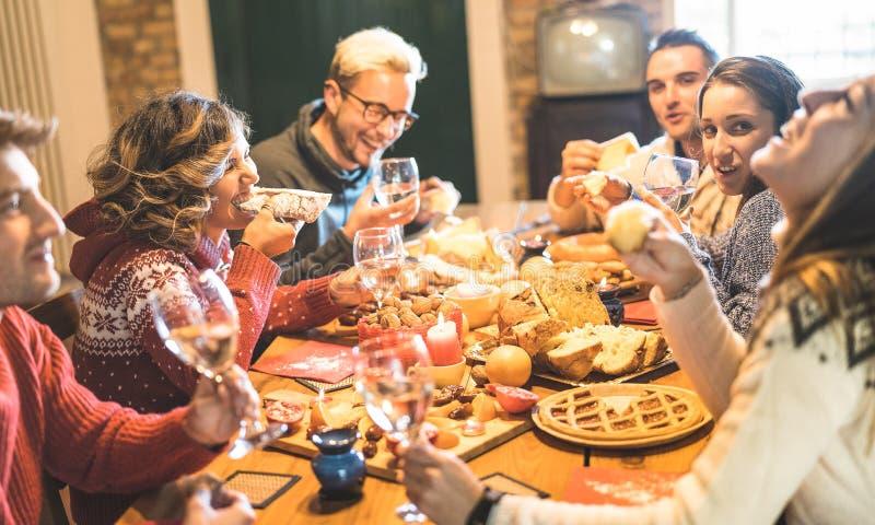 Οι φίλοι ομαδοποιούν την κατανάλωση των τροφίμων γλυκών Χριστουγέννων και την κατοχή της διασκέδασης στο κόμμα γευμάτων Χριστουγέ στοκ φωτογραφίες