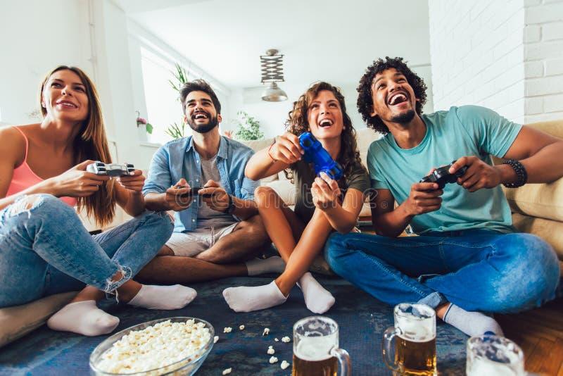 Οι φίλοι παίζουν τα τηλεοπτικά παιχνίδια μαζί στο σπίτι, που έχουν τη διασκέδαση στοκ φωτογραφίες