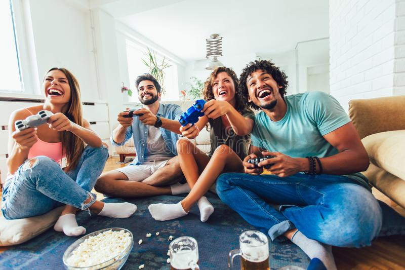 Οι φίλοι παίζουν τα τηλεοπτικά παιχνίδια μαζί στο σπίτι, που έχουν τη διασκέδαση στοκ εικόνες με δικαίωμα ελεύθερης χρήσης