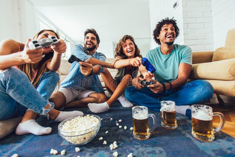 Οι φίλοι παίζουν τα τηλεοπτικά παιχνίδια μαζί στο σπίτι, που έχουν τη διασκέδαση στοκ εικόνες