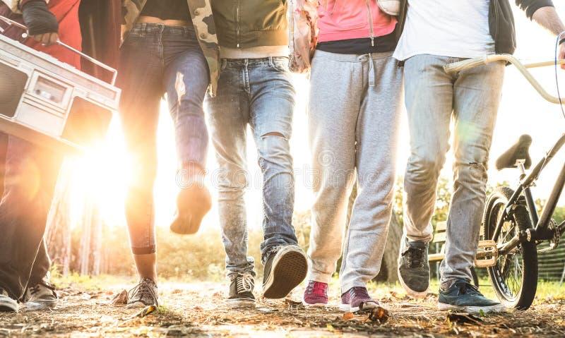 Οι φίλοι που περπατούν στην πόλη σταθμεύουν με το backlight και sunflare το φωτοστέφανο - έννοια φιλίας Millenial και πολυφυλετικ στοκ εικόνα με δικαίωμα ελεύθερης χρήσης