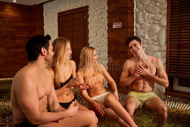 Οι φίλοι στο γέλιο μαγιό στο τζακούζι στη SPA στρέφονται στοκ φωτογραφία με δικαίωμα ελεύθερης χρήσης
