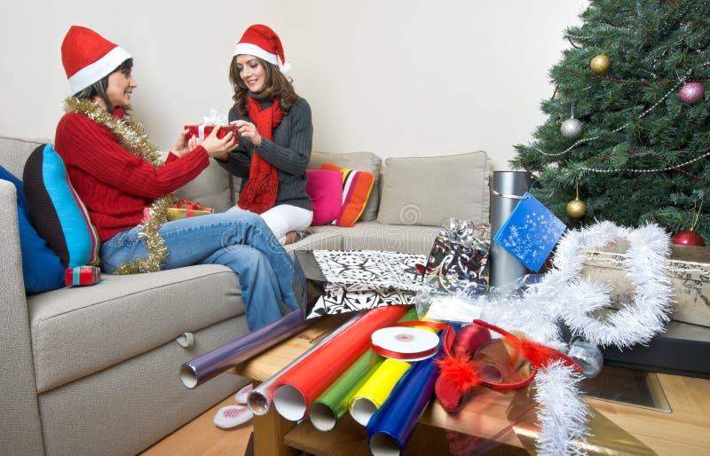 οι φίλοι Χριστουγέννων που ανοίγουν να προετοιμαστούν παρουσιάζουν στοκ εικόνες με δικαίωμα ελεύθερης χρήσης
