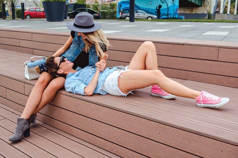 Οι φίλες κουτσομπολεύουν και έχοντας τη διασκέδαση υπαίθρια στοκ φωτογραφία