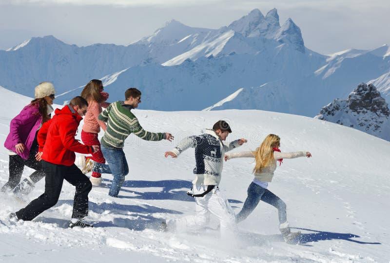 Οι φίλοι έχουν τη διασκέδαση στο χειμώνα στο φρέσκο χιόνι στοκ εικόνες