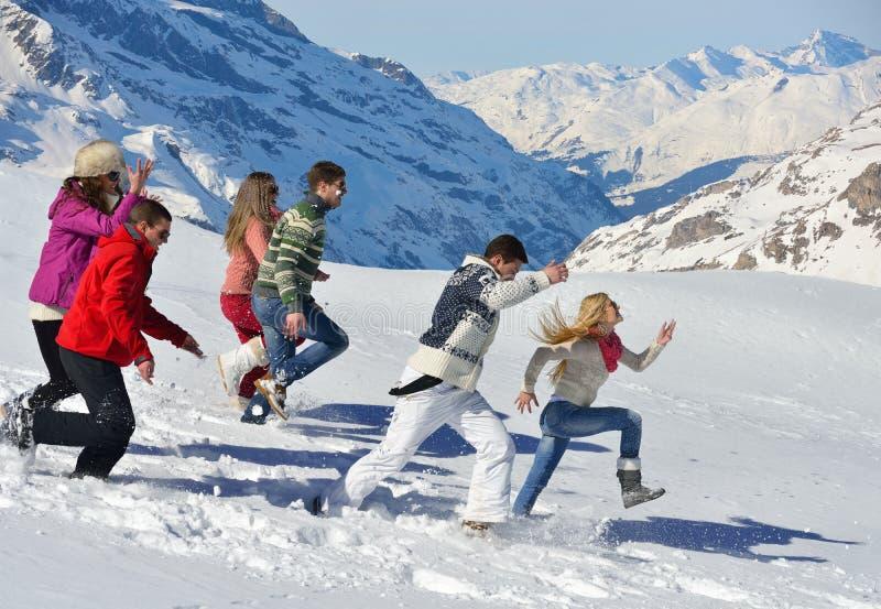 Οι φίλοι έχουν τη διασκέδαση στο χειμώνα στο φρέσκο χιόνι στοκ φωτογραφίες
