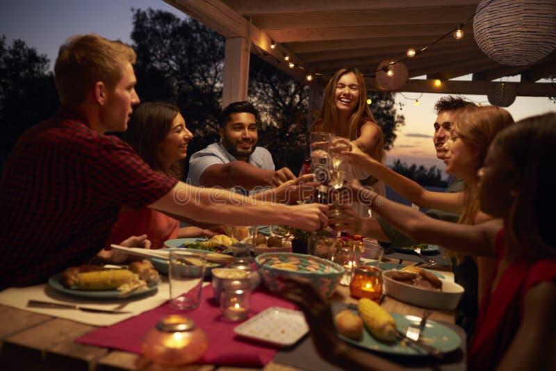 Οι φίλοι κάνουν μια φρυγανιά σε ένα κόμμα γευμάτων σε ένα patio, κλείνουν επάνω στοκ φωτογραφίες